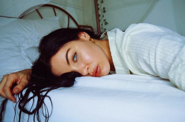 Sexy žena s modrými očami leží na bruchu v posteli.jpg