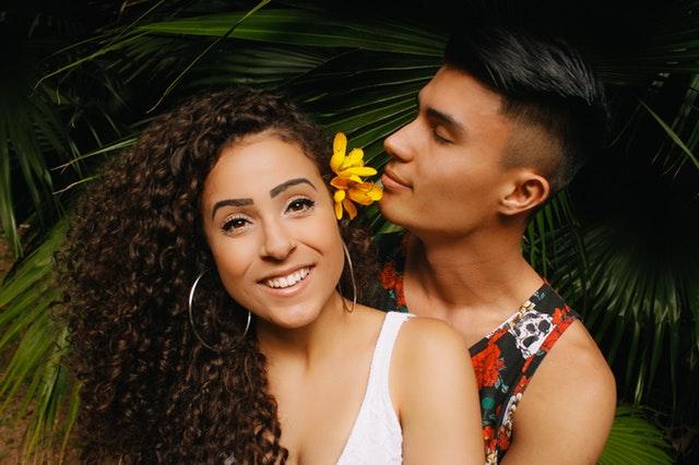 Muž objíma ženu s kučeravými vlasmi a kvetom vo vlasoch.jpg
