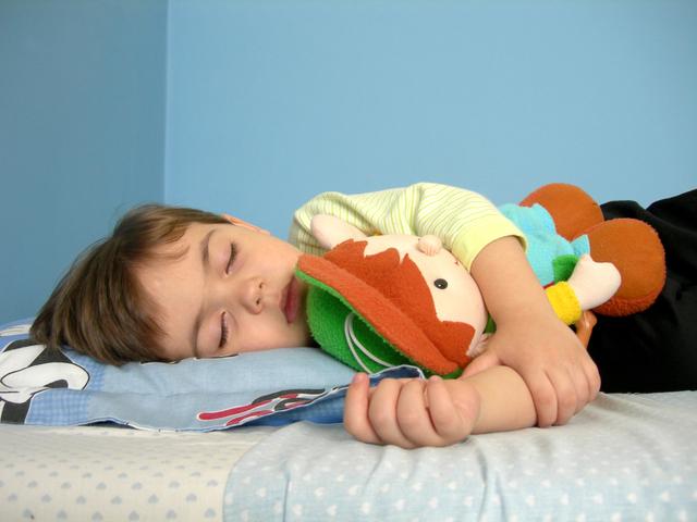 Malý chlapec pokojne spí v posteli