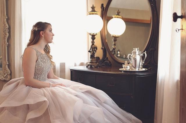 Dievča v ružových plesových šatách sedí pred zrkadlom.jpg