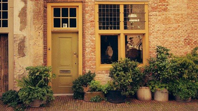 Tehlová fasáda domu s hnedými dverami a oknom.jpg