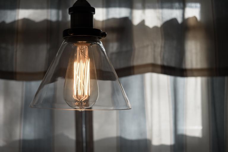 Lampa so skleneným tienidlom a zapálenou žiarovkou